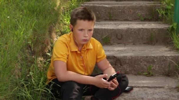 Smutný chlapec sedí u telefonu..