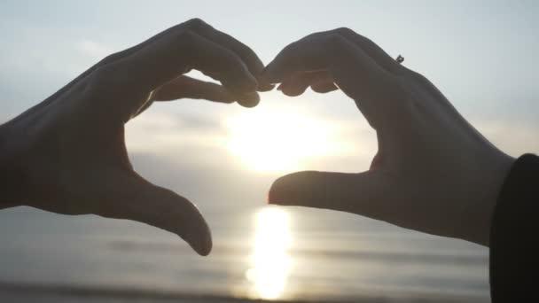 Pár, takže tvar srdce s rukama s západ slunce uvnitř na pláži v pomalém pohybu