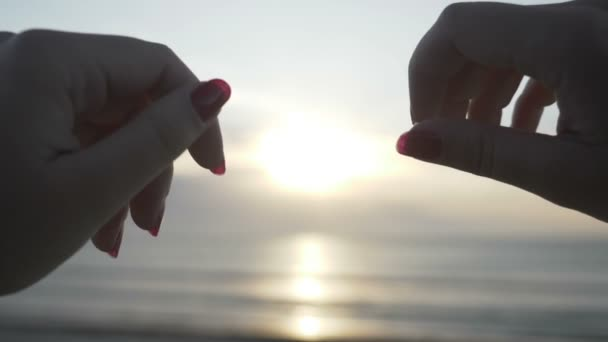 Sziluettje egy fiatal nő kezében viselt gyűrű, így a szív alakú a naplemente a tengerparton lassítva belső
