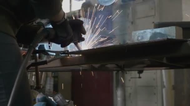 Schmiedin schweißt Metallteile, die in ihrer Werkstatt einen Funkenregen erzeugen