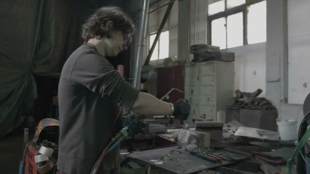 junge Schweißerin mit Schutzbrille und Vorbereitungen zum Schweißen eines Metalls in ihrer Werkstatt