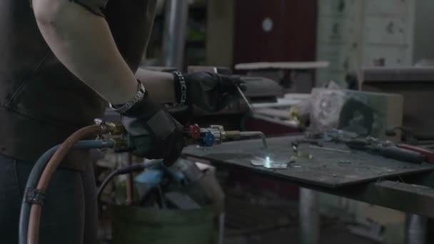 Nahaufnahme einer Schweißerin, die in ihrer Werkstatt zwei Metallteile schweißt