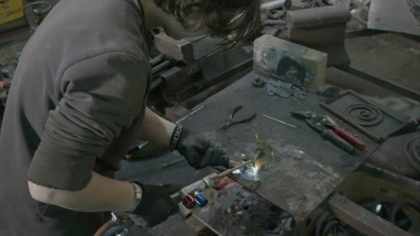 Mladá žena svářeč svařování kovů s nástrojem profesionální plamen v její dílně