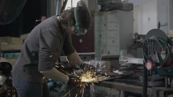 Schweißerin oder Schmied mit Schutzausrüstung vor Funkenflug schleift in ihrer Werkstatt glatten Stahl und Eisen
