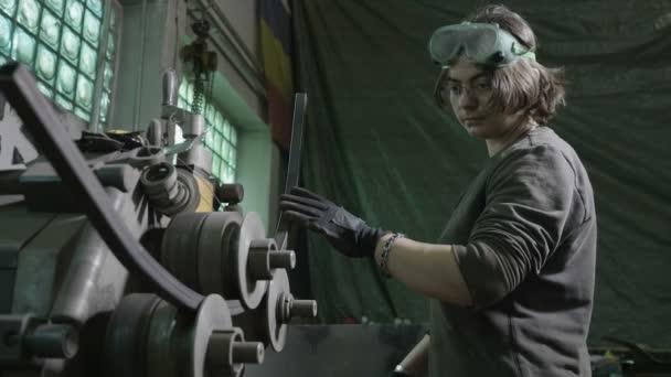 Schmiedin steckt in ihrer Werkstatt eine Eisenstange in eine Blechbiegemaschine