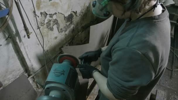 Schmiedin mit Schutzausrüstung poliert Metallschraube mit einem professionellen Rad in einer industriellen Fabrikwerkstatt