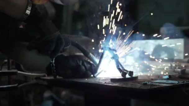 Zblízka žena svářeč nebo Kovář rukou oprava kovový předmět s svařovací stroj, který dělá jiskry v průmyslové výrobě