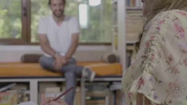 Profesionální psycholog žena poradenství mladého mužského pacienta a psaní poznámek během sezení v její kanceláři