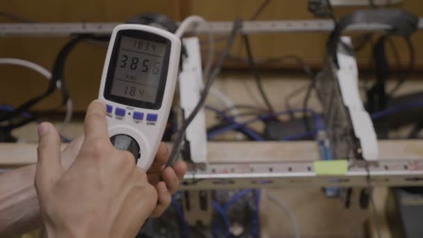 Closeup of technician controller hand setting up a power meter measuring gpu cryptocurrency mining rig electrical energy consumption.