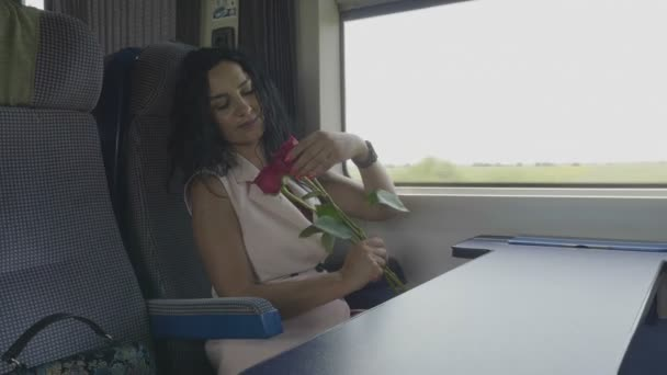 Young woman in love on train admiring roses received from her valentine love and travel concept