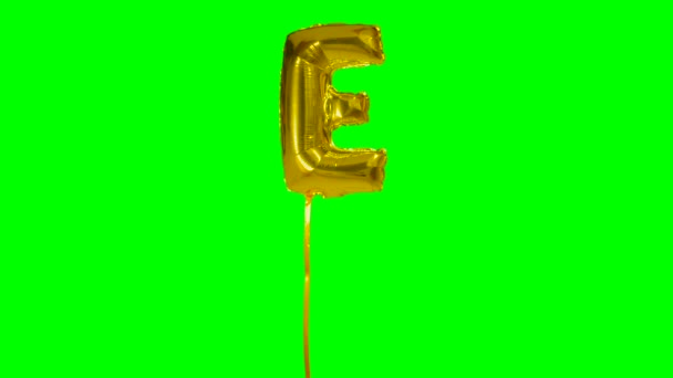 Letter E from alphabet helium gold balloon floating on green screen