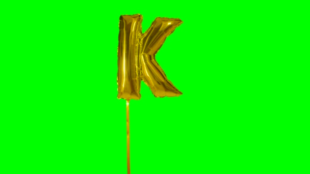 Letter K from alphabet helium gold balloon floating on green screen