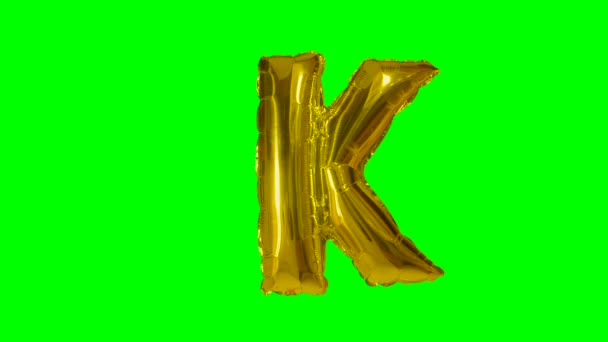 Big Letter K from alphabet helium gold balloon floating on green screen