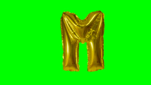 Big Letter M from alphabet helium gold balloon floating on green screen