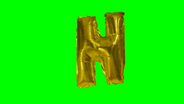 Big Letter N from alphabet helium gold balloon floating on green screen