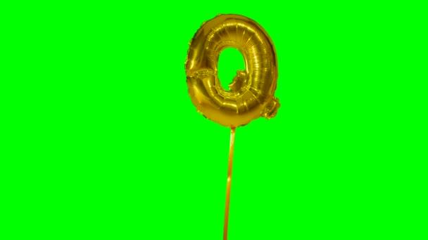 Písmeno Q abeceda helium zlato bubliny plovoucí na zelené obrazovce