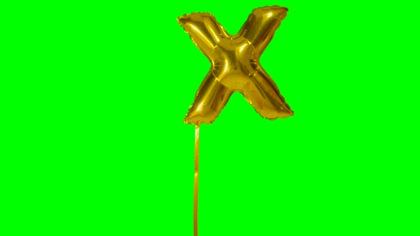 Letter X from alphabet helium gold balloon floating on green screen
