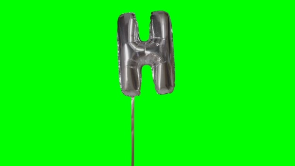 Letter H from alphabet helium silver balloon floating on green screen