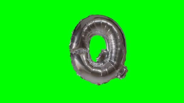 Nagy betű Q ábécé ezüst hélium léggömb lebeg a zöld képernyő