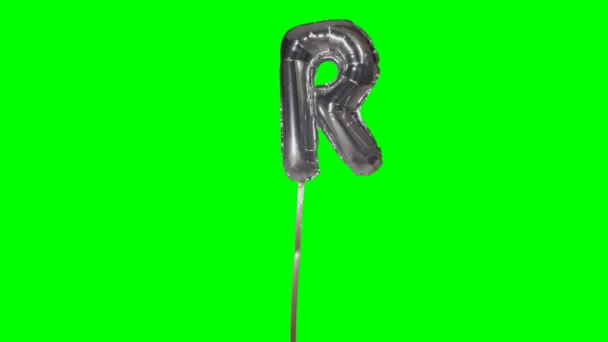 Letter R from alphabet helium silver balloon floating on green screen