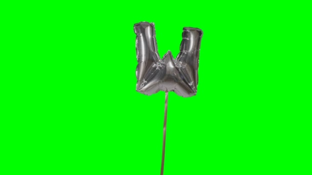 Letter W from alphabet helium silver balloon floating on green screen