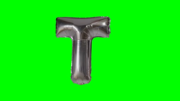 Big Letter T from alphabet helium silver balloon floating on green screen