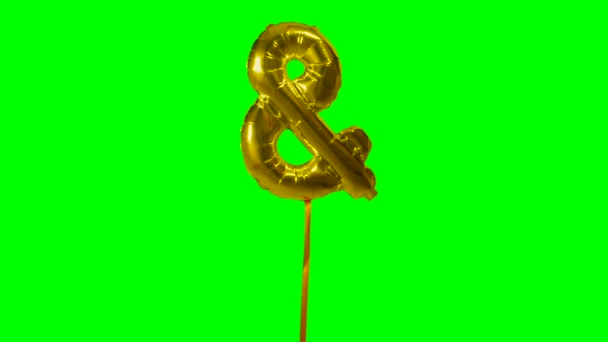 Sign symbol ampersand and from alphabet helium gold balloon floating on green screen