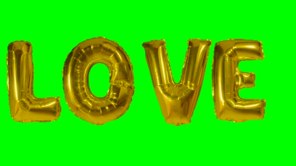 Word love from helium gold balloon letters floating on green screen
