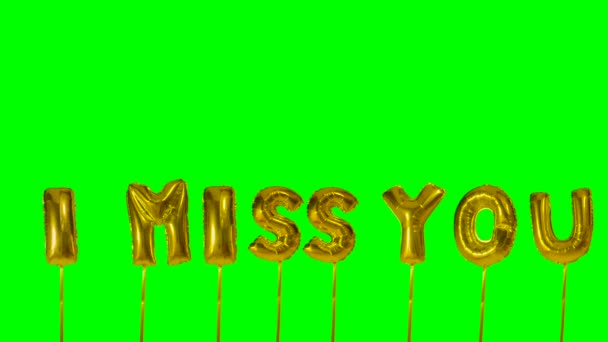 Word I miss you from helium golden balloon letters floating on green screen
