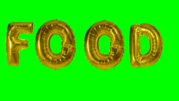 Word food from helium gold balloon letters floating on green screen