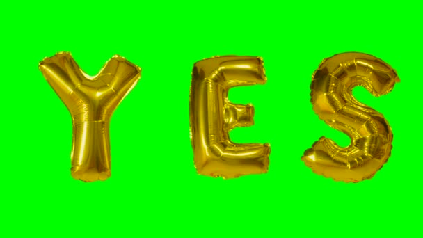 Word yes from helium gold balloon letters floating on green screen