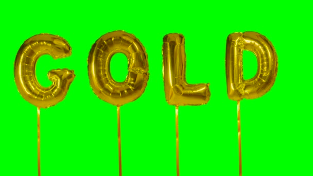 Word gold from helium balloon letters floating on green screen