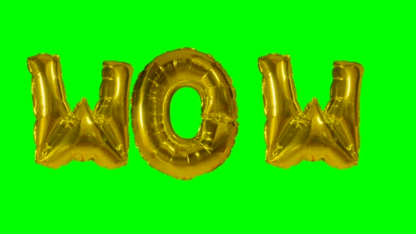 Word wow from helium gold balloon letters floating on green screen