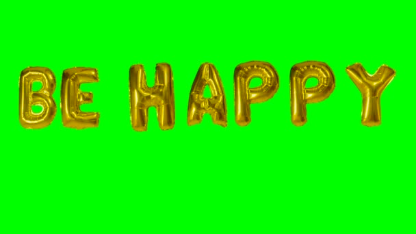 Word be happy from helium gold balloon letters floating on green screen