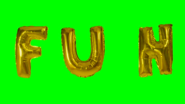 Word fun from helium gold balloon letters floating on green screen