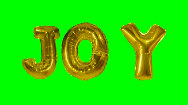 Word joy from helium gold balloon letters floating on green screen