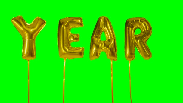 Word year from helium golden balloon letters floating on green screen