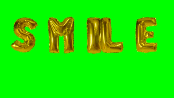 Word smile from helium gold balloon letters floating on green screen