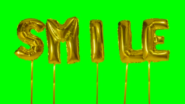 Word smile from helium golden balloon letters floating on green screen