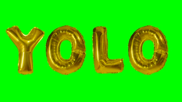 Word YOLO from helium gold balloon letters floating on green screen