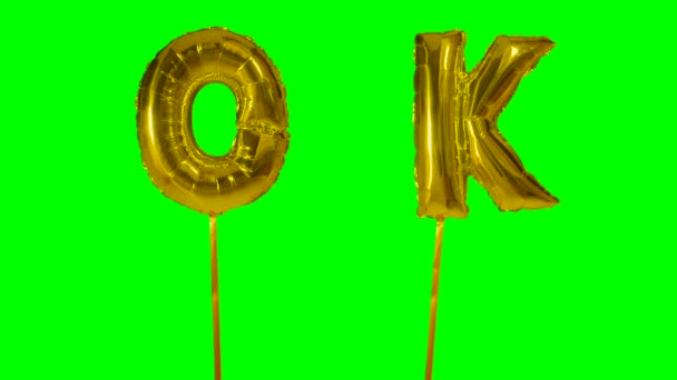 Word ok from helium golden balloon letters floating on green screen