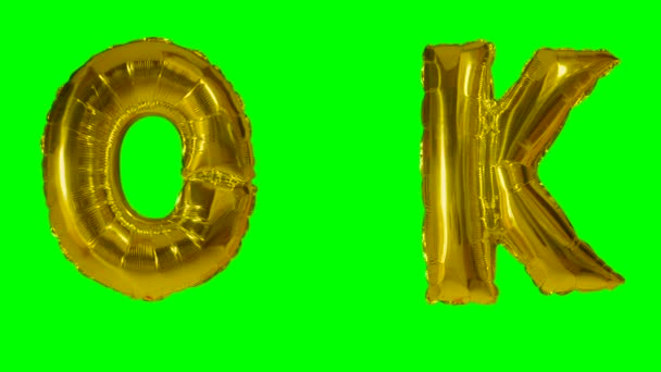 Word ok from helium gold balloon letters floating on green screen