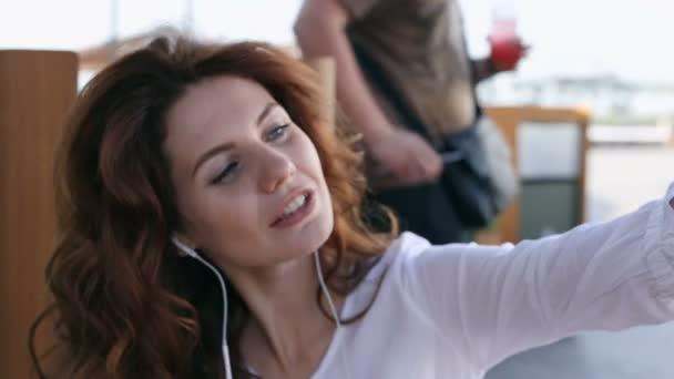 hübsche Frau mit lockigem Haar lächelt und macht Selfies.