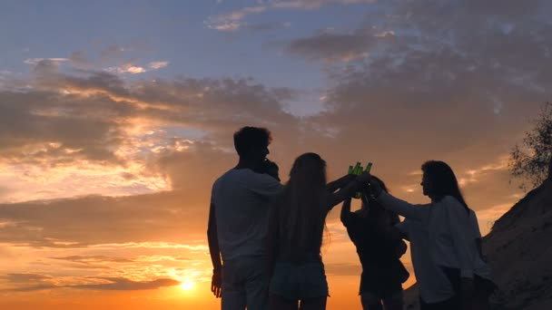 Friends clinking beer on the beach. Sunset. Slow motion.