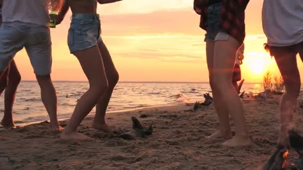 Dancing legs of friends on the beach. Beach party. Young man shooting video on the smartphone.