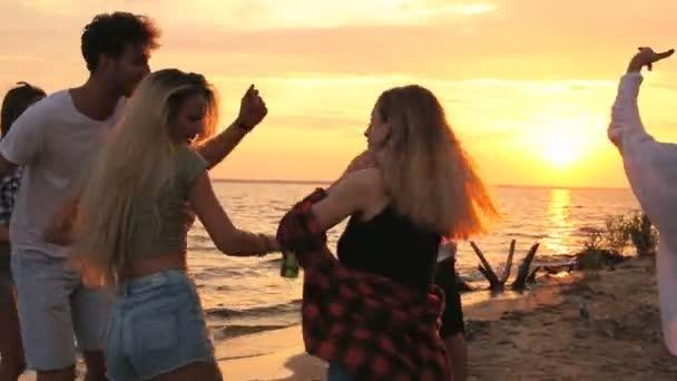 Skupina přátel tance na pláži. Čas západu slunce