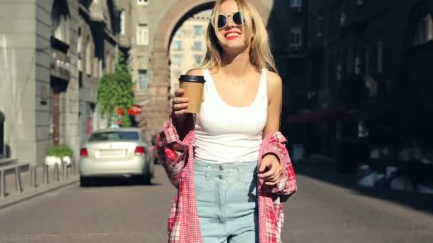 Young blonde wowam walking at the steet and drinking coffee. Steadycam shot.
