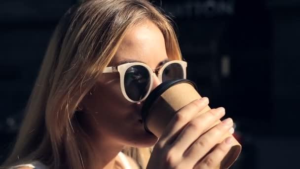Zavřete portrét atraktivní blond ženy pití kávy na ulici. Steadycam shot.