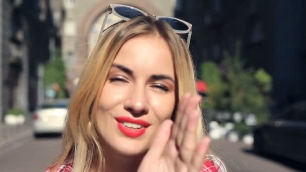 Young blonde woman doing air kiss and good bye gestures, going away.
