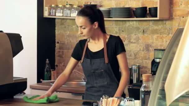 Coffee shop majitel (barista) designerské pracoviště a utírat prach na přepážce.